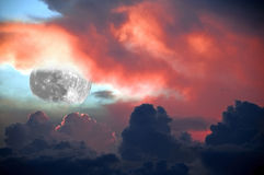 Fiery Lunar Sunset. Spectacular fiery sunset with a splash of blue sky and the moon lurking between the clouds for background Royalty Free Stock Images