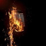 Fiery old fashioned microphone. A view of an old fashioned microphone on a stand, almost completely engulfed in flames.  Black background Stock Images