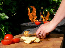 Fiery Outdoors Cooking. Close-up of an female chef preparing potatoes and tomatoes near the BBQ fire Stock Photography