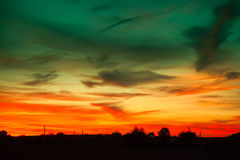 Fiery red sunset over the village. Rural landscape in evening at sunset with cloudy sky. Fiery red sunset over the village Stock Images