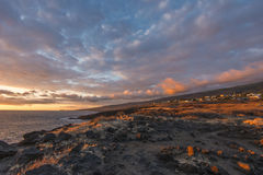 Fiery sky. A fiery sky with the last rays of the setting sun reflecting underneath the clouds near Etang Salé on Reunion Island in the Indian Ocean Stock Photo
