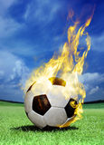 Fiery soccer ball on grass Stock Photos