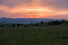 Fiery summer sunset. Over the the Almaj Valley with the mountains in the background and a meadow full of flowers in the foreground royalty free stock photography
