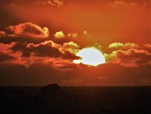 Dramatic Fiery Sun Surrounded by Clouds During Sunset. Sunset on the west coast Pacific Ocean. Vibrant orange red clouds are back lit by the sun Stock Images