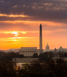 Fiery sunrise over monuments of Washington. Bright orange sunlight illuminates clouds over Washington DC at dawn at sunrise. Lincoln, Washington Monument and Royalty Free Stock Photos