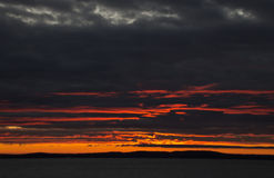 Fiery sunrise  on a stormy morning. Fiery sunrise with the sun obscured by dark storm clouds Royalty Free Stock Images