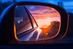 Fiery sunset as seen on the car`s side mirror stock photo