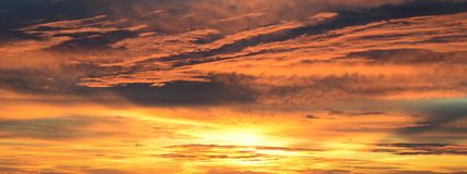 Fiery sunset banner image. Fiery sunset with a cloud filled sky royalty free stock photography
