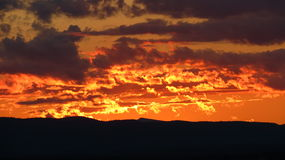 Fiery Sunset. Dark fiery orange sunset over distant mountains Royalty Free Stock Images