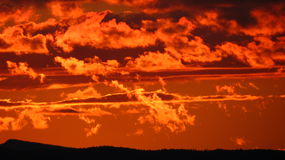 Fiery Sunset. Dark fiery orange sunset over distant mountains Royalty Free Stock Photo