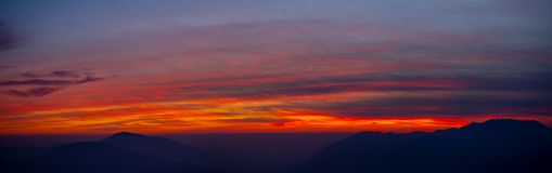 Fiery sunset from mountain peak in a cloudy evening. Fall season. Orobie mountains. Italian Alps. Fiery sunset from mountain peaks in a cloudy evening. Fall stock images