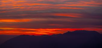 Fiery sunset from mountain peak in a cloudy evening. Fall season. Orobie mountains. Italian Alps. Fiery sunset from mountain peaks in a cloudy evening. Fall stock image