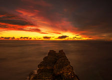Fiery sunset on pier. Long exposure of narrow rock pier covered with moss at sunset golden hour in Waikiki in Honolulu, Hawaii Stock Image