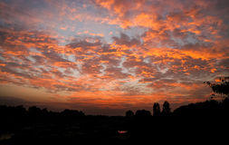 Fiery sunset scattered clouds Royalty Free Stock Images