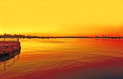 Fiery sunset on swan river with jetty-perth. Fiery sunset on swan river with the perth city scape and jetty landscape. Scene seemingly after bush-fire royalty free stock image