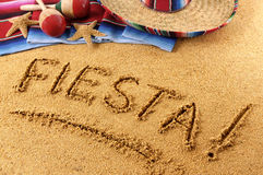 Mexican summer fiesta beach writing, sombrero. The word Fiesta written in sand on a Mexican beach, with sombrero, straw hat, traditional serape blanket, starfish Royalty Free Stock Photos