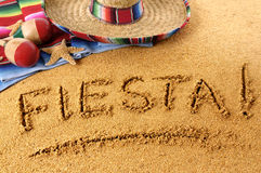 Mexican summer fiesta beach sand writing. The word Fiesta written in sand on a Mexican beach, with sombrero, straw hat, traditional serape blanket, starfish and Royalty Free Stock Photo