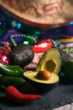 Fiesta: Cut Avocado With Jalepeno Peppers On Slate Board. A series of background images for Cinco De Mayo fiesta celebrations.  Margaritas, tacos, serape, lights Royalty Free Stock Photos