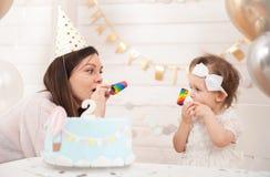 Fiesta de cumpleaños del bebé La madre y su hija celebran y diversión juntas Partido del niño con la decoración y la torta de los fotos de archivo