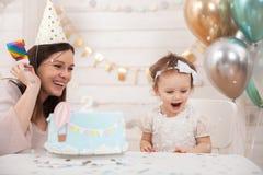 Fiesta de cumpleaños del bebé La madre y su hija celebran y diversión juntas Partido del niño con la decoración y la torta de los imagen de archivo libre de regalías