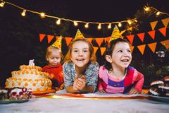 Fiesta de cumpleaños del ` s de los niños Tres muchachas alegres de los niños en la tabla que comen la torta con sus manos y que  Fotografía de archivo