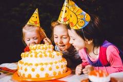 Fiesta de cumpleaños del ` s de los niños Tres muchachas alegres de los niños en la tabla que comen la torta con sus manos y que  Imágenes de archivo libres de regalías