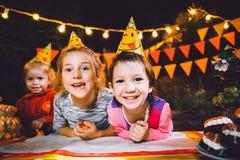 Fiesta de cumpleaños del ` s de los niños Tres muchachas alegres de los niños en la tabla que comen la torta con sus manos y que  Fotos de archivo libres de regalías