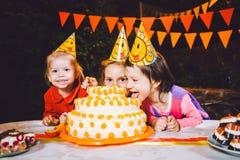 Fiesta de cumpleaños del ` s de los niños Tres muchachas alegres de los niños en la tabla que comen la torta con sus manos y que  Fotografía de archivo libre de regalías
