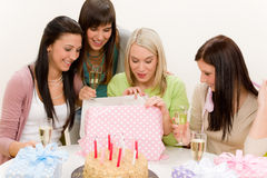 Fiesta de cumpleaños - la mujer desempaqueta el presente, celebrando Foto de archivo libre de regalías