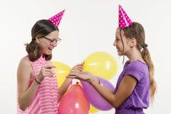 Fiesta de cumpleaños Los adolescentes de las muchachas dan un regalo Fondo blanco, en sombreros festivos con los globos Imagen de archivo