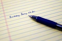 Fiesta de cumpleaños para hacer la lista en el papel con la pluma azul Fotos de archivo