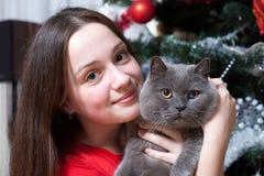 Fiesta de Navidad, mujer de las vacaciones de invierno con el gato Muchacha del Año Nuevo árbol de navidad en fondo interior Fotos de archivo libres de regalías