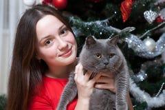 Fiesta de Navidad, mujer de las vacaciones de invierno con el gato Muchacha del Año Nuevo árbol de navidad en fondo interior Imagen de archivo