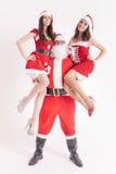 Fiesta de Navidad 2016 Papá Noel fuerte deteniendo a muchachas calientes Fotografía de archivo libre de regalías