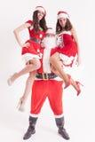 Fiesta de Navidad 2016 Papá Noel fuerte deteniendo a muchachas calientes Fotos de archivo