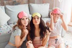 Fiesta de pijamas Mujeres jovenes en la máscara el dormir junto en casa que se sienta en piso que hacen muecas al primer juguetón imagenes de archivo