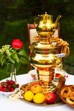 Fiesta del té de la primavera en el jardín, en una tabla cubierta con un blanco Fotos de archivo libres de regalías