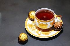 Fiesta del té de la tarde en un fondo gris Ingenio de la taza de oro de la porcelana Imágenes de archivo libres de regalías