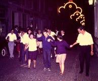 FIESTA-FEIERNDER, DIE IN EINE DER STRASSEN VON JACA, SPANIEN IM JAHRE 1965 SINGEN UND TANZEN Lizenzfreies Stockfoto
