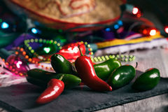 Fiesta: Hot Peppers On Slate Board With Party Decorations. A series of background images for Cinco De Mayo fiesta celebrations. Margaritas, tacos, serape, lights