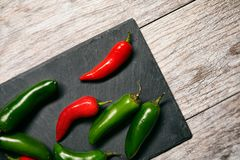 Fiesta: Jalepeno Peppers On Slate Cutting Board. A series of background images for Cinco De Mayo fiesta celebrations.  Margaritas, tacos, serape, lights, and Stock Photo