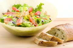 Fiesta salad. Fresh mixed salad greens, tomatoes, corn chips and cheese served in a 1950s era bowl, can you find the butterflies, with a potato rosemary loaf of Royalty Free Stock Photos