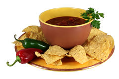 Fiesta Salsa & Chips. Bowl of salsa surrounded with tortilla chips and red and green jalapeno peppers, garnished with sprig of cilantro royalty free stock images