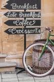 Fiets dichtbij een houten vat en wijzers waarop ontbijt, koffie, croissants wordt geschreven stock foto