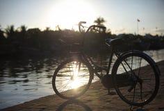 Fiets die door de rivier bij de zonsondergang in Europ wordt geparkeerd Royalty-vrije Stock Afbeeldingen