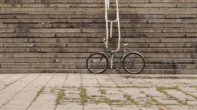 Fiets die van de staand vistuig de zwarte retro stijl zich op oude stedelijke uitstekende straat tegen tredenachtergrond bevinden Royalty-vrije Stock Afbeelding