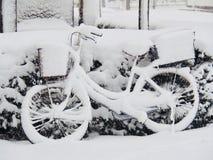 Fiets door Sneeuw in de Winterdag die wordt behandeld royalty-vrije stock afbeelding