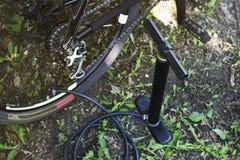 Fiets en luchtpomp in bosreparatiewiel van fiets Inflatiewielen met een pomp met een drukmaat Stock Foto