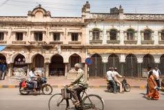 Fiets en meeslepende motorfietsen op historische straat van Indische stad Stock Foto