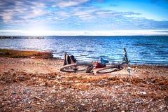 Fiets en rugzak die op de wilde overzeese kust liggen Stock Foto's